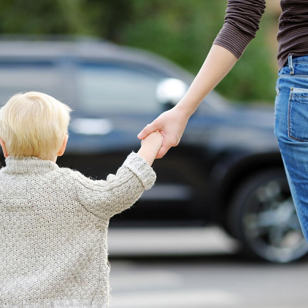 Eine Mutter führt ihr Kind über eine stark befahrene Strasse. Das ist unser Verständnis von Personenschutz